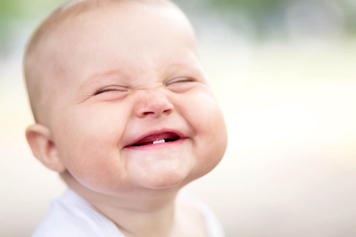 A baby grins showing two teeth. Irresistible smiles at Manor Dental Health. If you can't get away with this look, let us transform yours.