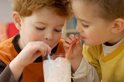 Tow young children share a milkshake. Concerned about your child's dental health and sugar consumption? Speak to Nick Allday at Manor Dental Health in Hull
